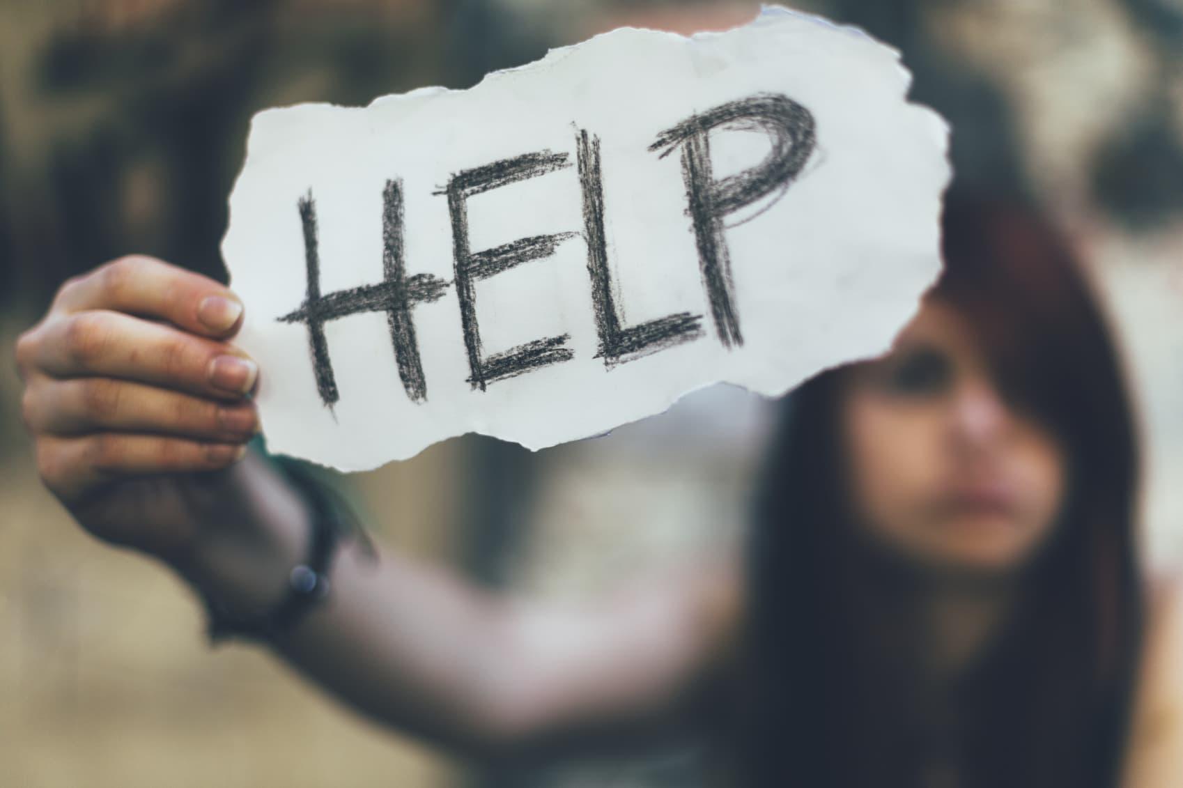 Teenage girl holding help board